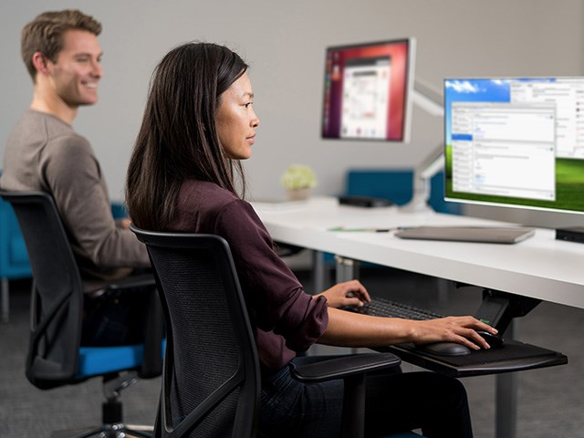 two people sitting at smartfit desk with monitor arms