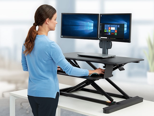 person at sit stand desk with monitor arm