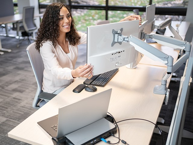 person adjusting dual monitor arm at desk